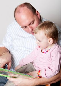 Father and baby daughter reading